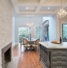 pretty kitchen with stone wall fireplace, big windows, wood floor, chandeliers, coffered ceiling