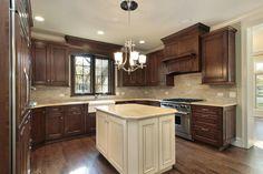 Dark kitchen cabinets with white middle work island.