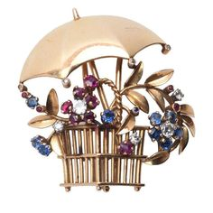 Retro Ruby Sapphire Diamond Gold Umbrella Clip Brooch. Retro yellow gold brooch of a stylised flower basket with an umbrella. Flowers gem set in Ruby, Sapphire and Diamond. In total, 9 round cut diamonds with an approximate weight of 0.50ct, 10 round cut sapphires and 11 round cut Rubies. Circa 1940s.