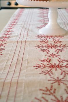 Snowflakes cross-stitched on a table runner ... or even just a piece of cloth.