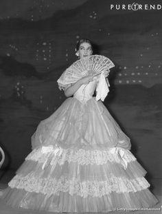 Maria Callas joue les majestueuses avec un large éventail et une robe volumineuse.