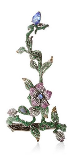 This bracelet with an attached ring by Wendy Yue features vines and flowers encrusted with colored sapphires, diamonds, tanzanite, and tsavorite stones set in 18k white gold.
