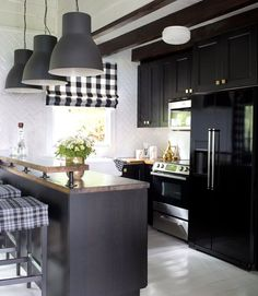 A new breakfast bar shrank the room's size but boosted its storage. The butcher-block countertops, black cabinetry, large industrial pendant lights, and a porcelain apron sink—all from Ikea!—kept costs down without sacrificing style, while black appliances (less expensive than stainless ones) match the cabinets for a seamless effect. - CountryLiving.com