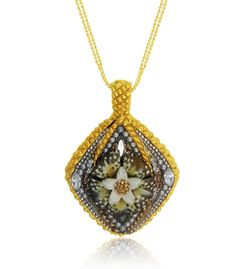 Add pizzazz to any outfit quickly and easily. The bale and top portion of this pretty pendant is reminiscent of a pineapple with golden layers that highlight a spectacular Swarovski crystal flower blooming from the center. A feathered-like background gives this beautiful piece additional glamour. What a great choice for weekdays, weekends or weddings! Crafted in sterling silver and plated in warm 24K gold, this dashing pendant is a radiant mix of texture and design…