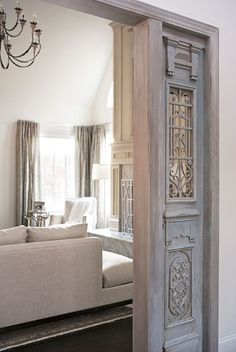 Now this is a great idea for those wide openings into dining rooms and family rooms where sometimes too much moulding can be used or nothing at all! Great Pin! Antique doors frame the opening into the living room...