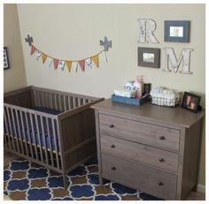 Little boy's nursery.  Little man's cozy little nook.  Travel theme. Ikea Sundvik crib in grey brown, Hemnes grey brown dresser, map initials, framed post cards, bunting, airplanes