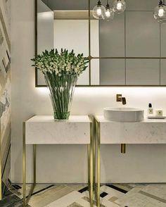 """Na """"vibe"""" dos metais dourados um lavabo muito lindo com detalhes em ouro escovado no espelho e na bancada."""