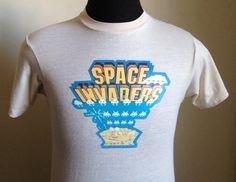 Vintage 1980s tan Space Invaders t-shirt from 1981, with multicolored image and print.    Size: Lmedium, 38-40  Brand: Hanes Fifty-Fifty Combed  50% cotton, 50% polyester    The shirt is very soft and in very good vintage condition, with no visible tears - though light speck next to image.    Approximate measurements with garment laying flat (INCHES):  Length (from top of shoulder at collar seam to bottom) : 24.5  Sleeve (from top of shoulder seam to cuff edge) : 6.5  Between Shoulder Seams…