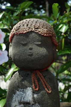 Jizo, adorned in baby cap, each one has a different story to tell