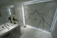 Statuary #marble #flooring, backlit book matched wall cladding, #vanitybench, and #showertray