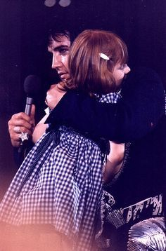 Elvis Hugging Little Girl On Stage 1975 by Marija. This little girl is blind and was standing at the end of the stage.. Elvis had His Dr look at her and have some testing done. He paid for her corrective surgery so she could see....