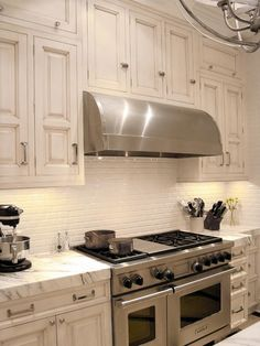 White Subway Tiles  Medium-sized white subway tiles give this contemporary, cottage-style kitchen a cool, urban feel. When paired with soft, marble countertops and distressed cabinets, the look is instantly sophisticated.