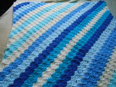 Corner 2 corner afghan with us...What an Excellent job she did, I love the striping and the colors...First attempt of C2C blanket, 3 sides completed, one more to go, to fit double bed, used Dk and 4.00 hook.... pattern and video link here: http://www.thecrochetcrowd.com/.../1260-cornertocorner.html