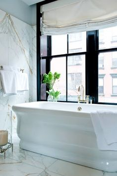 Bathroom with large white veiny marble slabs (probably a Calacatta gold marble), a stand alone porcelain tub, and glossy black trimmed windows