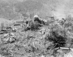 Two light machine gunners cover men of the 187th RCT as they go up a ridge on Hill 451, north of Inje, Korea, while F-80's strafe the village.   1 June 1951. Korea.   Signal Corps Photo #8A/FEC-51-17706 (Turner)