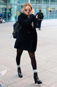 Margot Robbie usa look total black com mochila e botas pretas