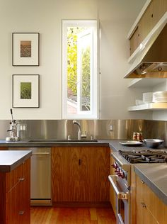 Kitchen Design Idea - Install A Stainless Steel Backsplash For A Sleek Look | Stainless steel panels wrap around the walls of this kitchen to make for easy clean up after a messy meal.