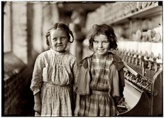"January 1909. Two of the ""helpers"" in the Tifton Cotton Mill at Tifton, Georgia. They work regularly. Photo and caption by Lewis Wickes Hine. I can only hope that these two precious little girls aren't barefooted, but fear they are. And, I can only pray that their later years in life continued to reflect their adorable smiles from the attention of the photographer."
