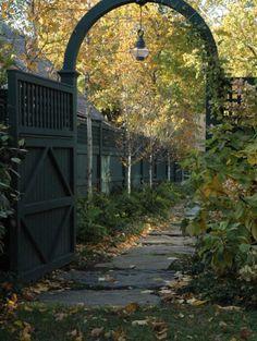 Jardín con puerta de arco metálica - by Timothy Lee Landscape Design