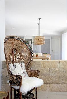 """Trône de rotin... Chiné chez Emmaüs, ce magistral fauteuil en rotin, icône des films érotiques """"Emmanuelle"""", est ici habillé d'une (fausse) peau de mouton et d'un coussin """"Simba"""" (AM.PM.). © Elodie Rothan"""