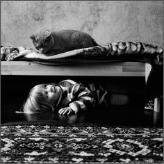 """Andy Prokh, fotógrafo russo segue a filosofia de que """"um fotógrafo deve captar aquilo que ama"""" – como tal, Prokh decidiu fotografar a amizade da filha Catherine com o seu gato, Lilu. A série de imagens a preto e branco, conta a """"história de amor"""" entre a criança e o felino ao longo de alguns anos, sempre com cenários e temáticas originais."""