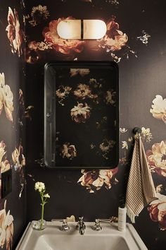 Vintage-inspired black floral wallpaper adds charm to a powder room,