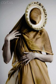 Woman wrapped in gold fabric with a frame around her face http://fotochannels.com/zoom/42-28523554/