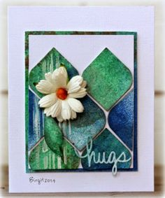 """Birgit at Rapport från ett skrivbord created this card using die cut shapes coloured with Colour Bloom sprays, flower and Technique Tuesday """"Say It-Hugs"""" die."""
