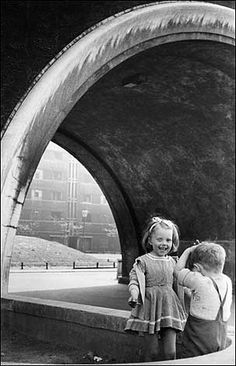 Children playing by archway, Quarry Hill Flats, Leeds 1954.. c/o © Marc Riboud.