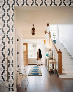 A wide hallway with a blue patterned rug and a white-and-grey staircase