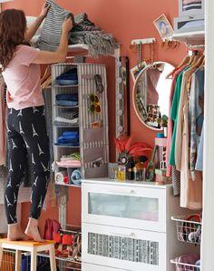 Vista de una mujer subida a un taburete colocando unas alfombras encima de los estantes de un sistema de armario abierto.