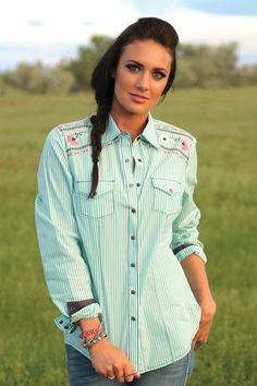 A flattering arena fit defines the shape of this mint green striped, long sleeve. Double front pockets, contrast trim and matte gun metal snaps keep it true to western style, while floral embroidery a