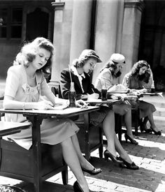 A group of 1940s female students doing their schoolwork outdoors.