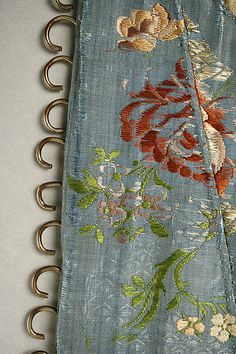 Detail front, corset, United States or Europe, 18th century. Brocaded blue silk with multicoloured flower motifs, linen lining, metallic lace trim.