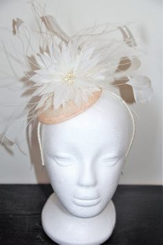 This is a pretty handmade bridal fascinator. It has a pale pink sinamay base and a large ivory feather flower, which is decorated with hand stitched cream pearls and ivory feathers. The fascinator comes on an ivory hairband.  This item is also available in other colours. You can have a black, cerise or navy flower and feathers on an ivory base with an ivory hairband. There is currently 1 item available in the ivory and pink, which can be shipped within 1 - 2 business days, However, if you…