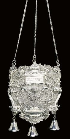 AN IMPORTANT GERMAN SILVER TORAH SHIELD  Mark of Rötger Herfurth (Scheffler 444), Frankfurt am Main, circa 1770  Cartouche-shaped & chased with dense rocaille, flowers & C-scrolls on a matted ground, upper part chased with Lions of Judah & a crown centering a rectangular compartment with five interchangeable festival plaques, double-sided & inscribed in Hebrew, lower part with a cartouche engraved with a Hebrew presentation inscription, with three pendant bells beneath, marked on shield...