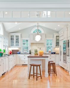 Super light and bright white kitchen gets warmth from the rich wood floor and pops of color from the countertop accents (via David Sharff, A...