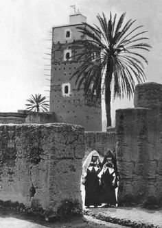 An old picture of two women, close to the Old mosque of tiznit, The mosque and the Palm, are still in their places.