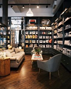 Midcentury Modern Retail Store Design - Gray built-in shelving surrounds a seating area at Dwell Studio.