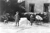 New Alresford: Jack and Geoffrey Walford making a snow castle in the garden of Arlebury House, with Bettine Walford in a pram nearby, December 1906