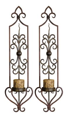 """These wall sconces are made of hand forged metal finished in a combination of mahogany rust and olive bronze. Antiqued candles included. 8""""W x 30""""H x 6.5""""D"""