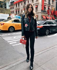 An embroidered leather jacket with a sweater, a satchel, jeans, and ankle boots.