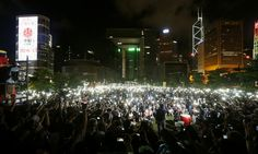 Pro-democracy protesters switch on their mobile phones during a campaign to kick off the Occupy Central civil disobedience event in front of...