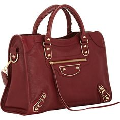 Balenciaga brick red glazed, grained goatskin Metallic Edge City bag. Exterior tassel-trimmed zip pocket, metal buckles and studs at front, polished goldtone h…