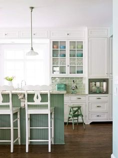 White kitchen with painted island. The mini cabinets in the sofit area is a nice change.