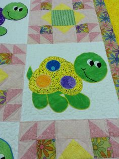 Sunny yellow, soft pink and lime green are colors to describe this non traditional colored baby quilt. Satin stitched appliqued Turtles and Summer Winds quilt blocks combined to make an adorable quilt for any young lady. Bright multi colored daisy floral on the backside, tie this all