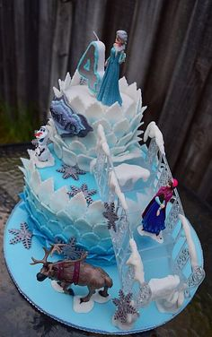 Two-tiered ombre Disney Frozen cake with ice staircase.