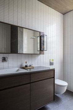 In This Master Bathroom, Small White Rectangular Tiles Cover The Walls From  Floor To Ceiling, And Dark Elements Like The Bath And Vanity Compliment The  ...