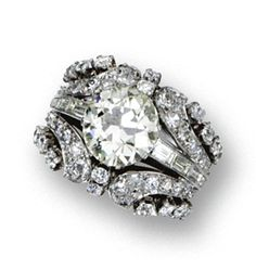 DIAMOND RING, CIRCA 1950 Set with an old European-cut diamond weighing 4.26 carats, flanked by 14 baguette diamonds, within an openwork jacket of scroll design set with 68 old European-cut and single-cut diamonds, altogether weighing approximately 2.00 carats, mounted in platinum