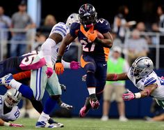Knowshon Moreno (27) of the Denver Broncos gets some air while running past J.J. Wilcox (27) of the Dallas Cowboys during the first half of ... #ProFootballDenverBroncos